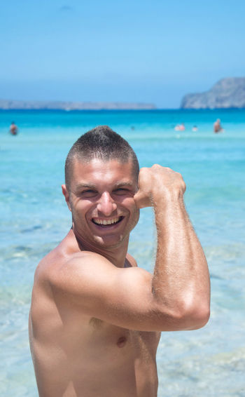 Portrait Of Smiling Shirtless Man Flexing Muscles At Beach