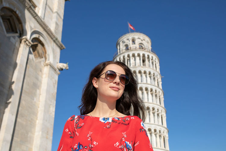 Woman wearing sunglasses while standing against leaning tower of pisa
