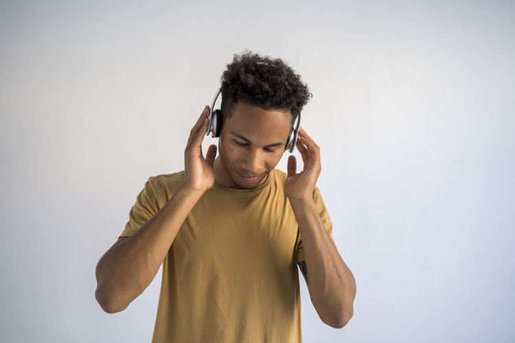 Close-up of man with headphone against white background
