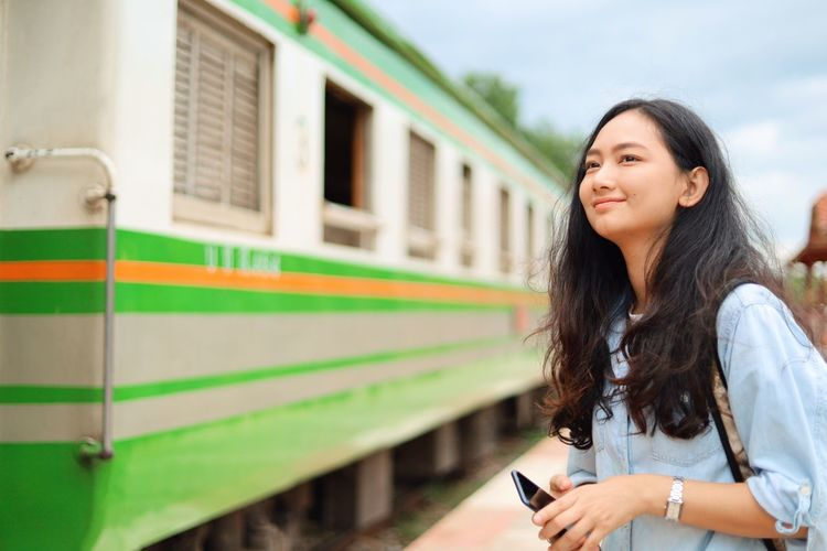 Technology Young Adult Long Hair One Person Young Women Women Hair Holding Mobile Phone Lifestyles Hairstyle Rail Transportation Mode Of Transportation Standing Communication Beauty Adult Train Public Transportation Wireless Technology Beautiful Woman Outdoors