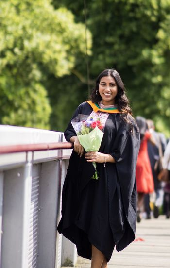 Portrait of young woman wearing graduation gown while standing on footpath against trees