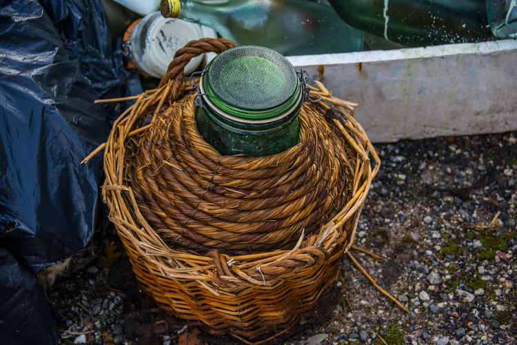 Vintage green glass flask covered with wicker on the street