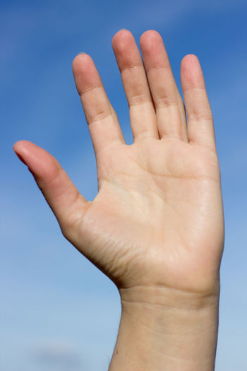 Close-up of human hand against sky