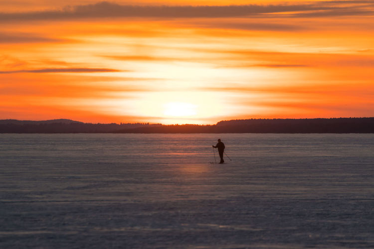 Sky Ski Skiing Scenics - Nature Beauty In Nature Tranquility Tranquil Scene Nature Canada Coast To Coast Orange Color Orange Orange Sky Sunset Silhouette Water One Person Real People Lifestyles Cold Temperature Cloud - Sky Non-urban Scene Land Winter Standing Ice Outdoors