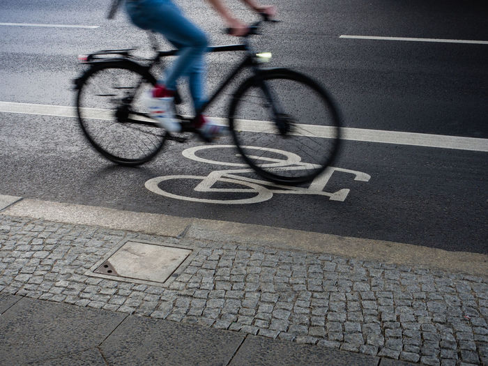 Bicycle Transportation Activity Motion City Cycling Street Sport Blurred Motion Road Healthy Lifestyle Speed Riding Sign Ride Lifestyles Exercising Outdoors Human Limb Low Section Bicycle Lane Road Asphalt Sidewalk Road Marking Moving Biker Wheel