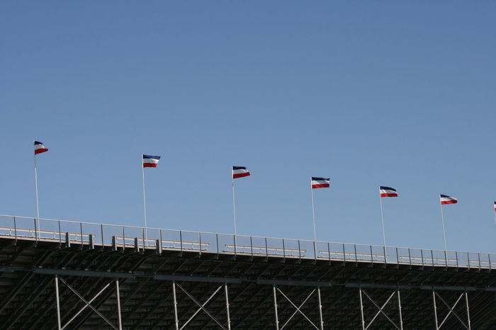 Built Structure Clear Sky Day Flag Flags In The Wind  Grandstands Low Angle View No People Outdoors Perspective Perspective Photography Seats Sky Stadium Staircase Stairs Stands