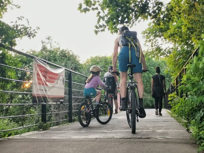 Rear view of people riding bicycle