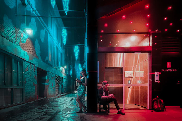 Digital composite image of woman walking on illuminated street amidst buildings at night