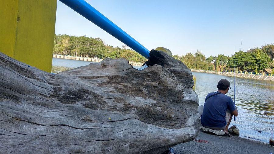 Rear view of boy sitting on rock against sky