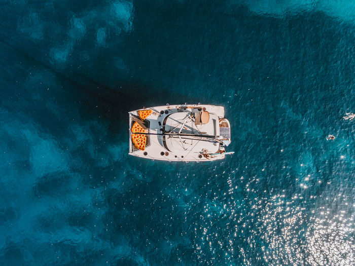A catamaran sailing yacht with pizza floaties atop sailing over beautiful deep blue mediterranean waters. Catamaran Drone Shot EyeEm Best Shots Holiday Mediterranean  The Week on EyeEm Aerial View Beauty In Nature Dji Drone Photography High Angle View Nautical Vessel No People Outdoors Paradise Sailboat Sailing Sea Ship Transportation Vacation Yachting A New Beginning Springtime Decadence