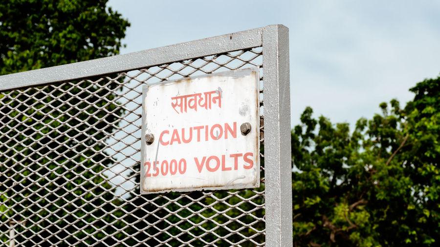 Warning information sign on metal fence against sky