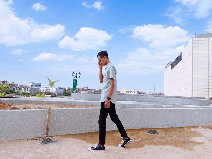 Full length of young man standing against sky in city
