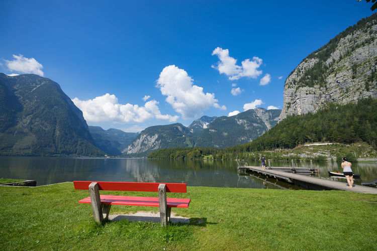 Empty Bench By Lake Against Sky