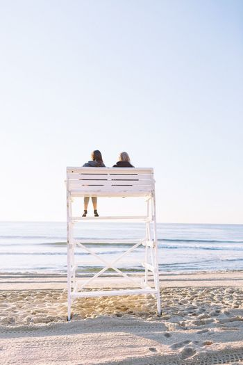 Rear View Of Couple Sitting On Lifeguard Hut On Sand At Beach Against Sky