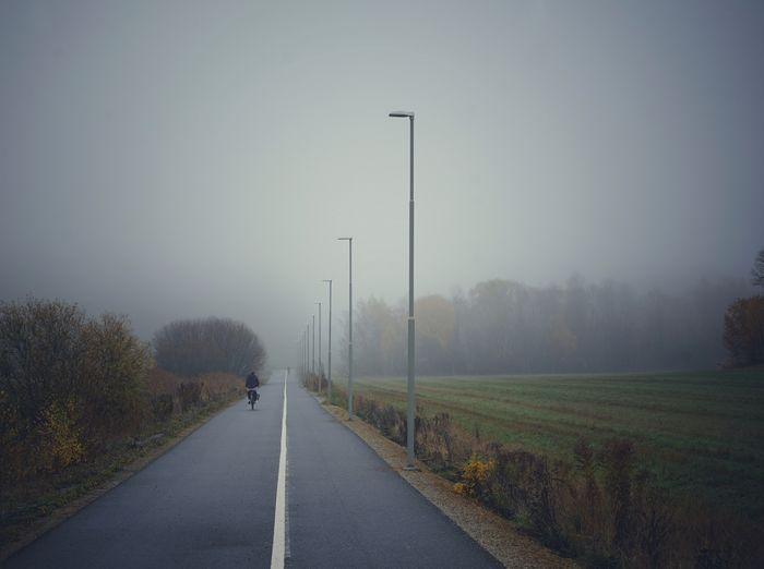 Road amidst field against sky during foggy weather