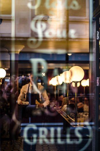 Waiter at restaurant seen through glass