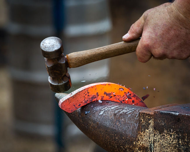 Hammer and hot horseshoe on anvil Anvil Hammer Heat Occupation Metal Manual Worker Outdoors Hand Human Hand Hand Human Body Part Holding One Person Focus On Foreground Close-up Outdoors Activity Day Men Industry Metal Adult Orange Color Industry Working Finger
