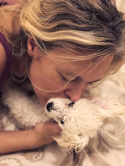 Close-Up Of Mature Woman Kissing Dog On Bed