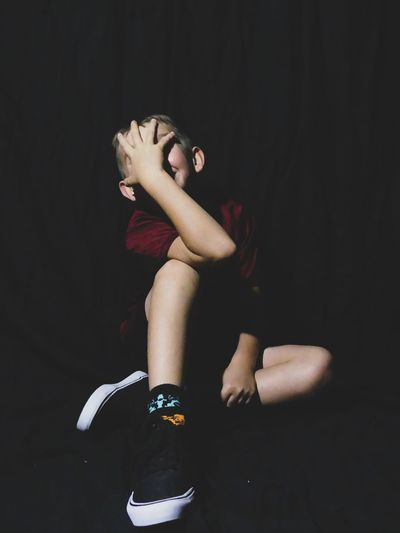 Boy covering face while sitting against black background