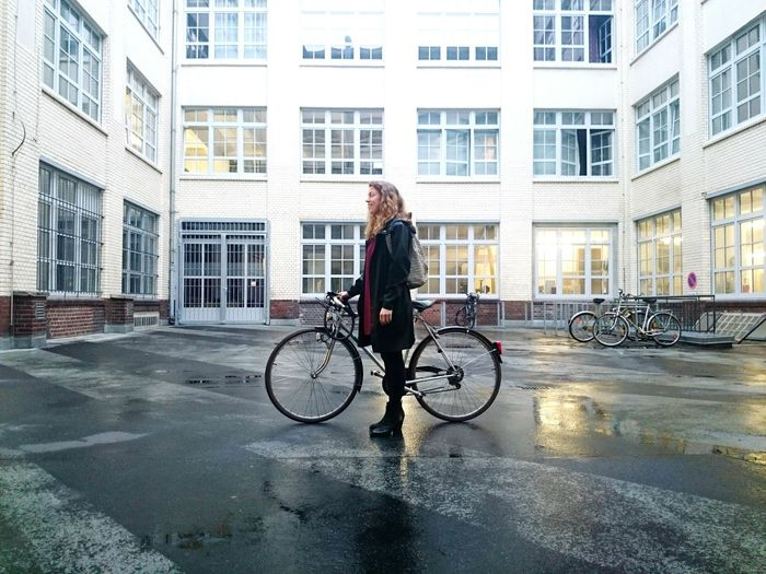 Full Length Side View Of Woman Standing With Bicycle On Street In Front Of Buildings