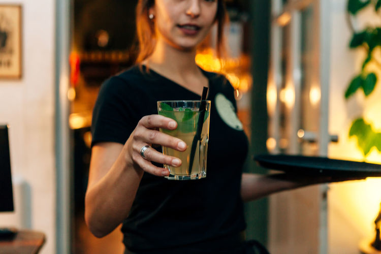 front view of a waitress serving a drink taken from the tray that she holds on the other hand Cocktail Adult Bartender Casual Clothing Catering Communication Drink Focus On Foreground Food And Drink Front View Glass Holding Leisure Activity Lifestyles Mojito Nightclub One Person Refreshment Restaurant Serving Size Standing Waist Up Women Young Adult Young Women