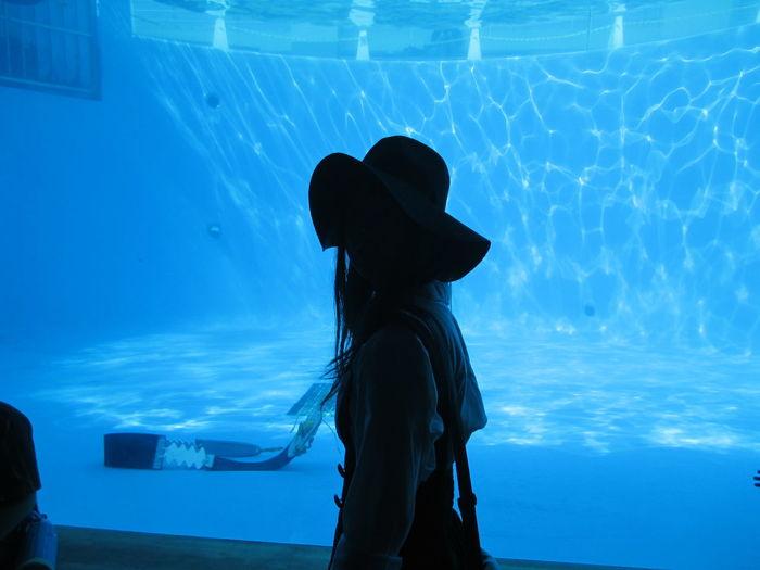 Woman standing against aquarium