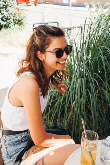 Young woman with sunglasses on table