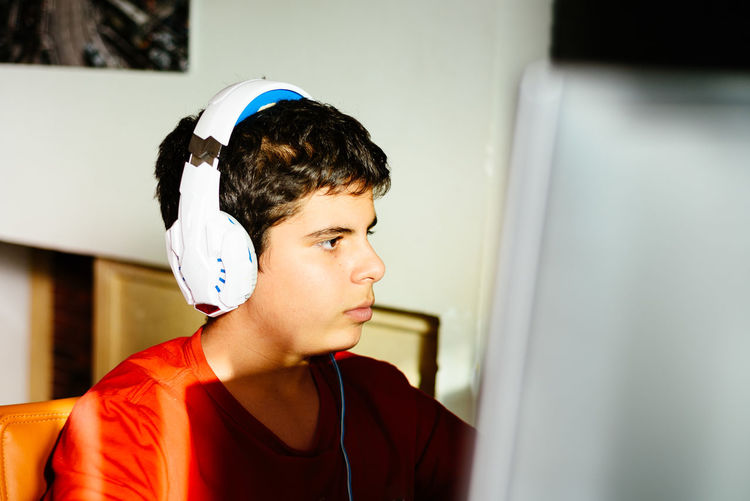 Close-up of boy playing video game at home