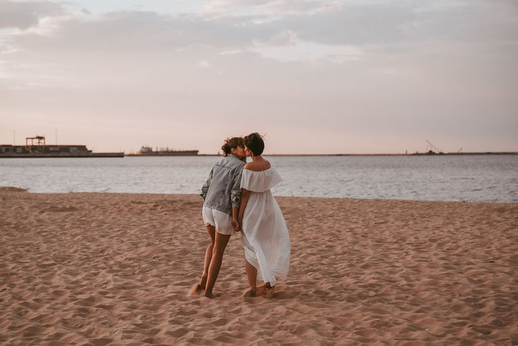 Two women walking on the beach and kissing.