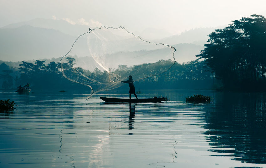 Fisherman casting out his fishing net in the river by throwing it high up into the air early in the blue colored morning to catch fish with his little fishing boat. Asian Culture Beauty In Nature Casting Catching Early Morning Fisherman Fishing Fishing Net Fishingnet Lake Men Misty Morning Morning Nature Nature Nautical Vessel Net One Person Outdoors Real People Riverbank Scenics Silhouette Water Waterfront