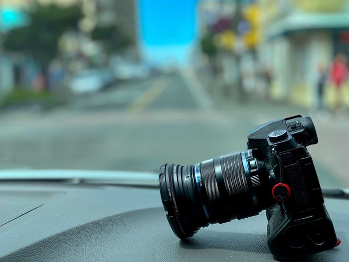 Close-up of camera against cars