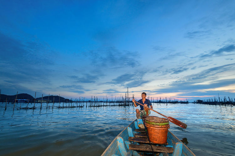 Traditional colorful asian fishing boats in fishing village Agriculture Beauty In Nature Boat Cloud - Sky Fisherman Fishing Lake Landscape Nature Nautical Vessel One Person Outdoors Real People Scenics - Nature Sea Seascape Sky Sunset Transportation Travel Destinations Water