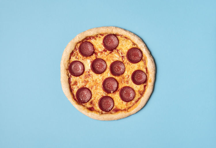 Tasty pizza salami with melted cheese, mozzarella and tomato sauce on a blue background.