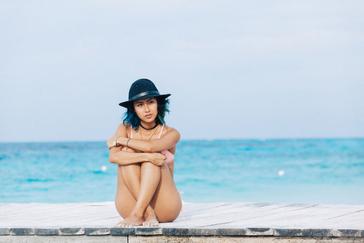 Full length of woman in bikini sitting on pier against sea and sky