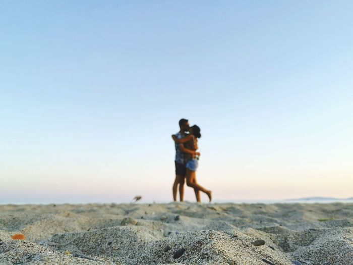 Close-up of sand with couple kissing in background at beach