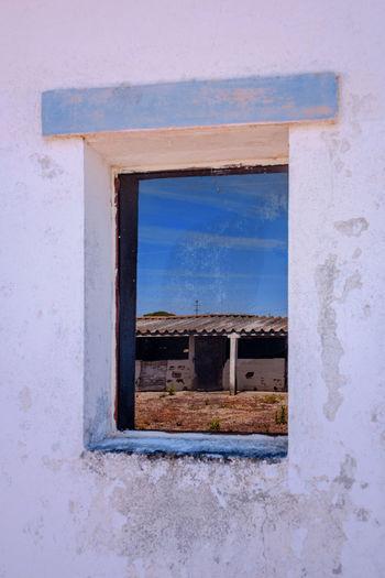 Buildings against blue sky seen through window