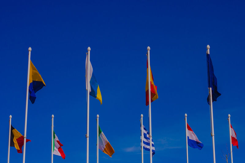 Low angle view of various flags against clear blue sky