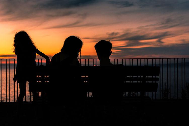 Silhouette people standing on railing against orange sky