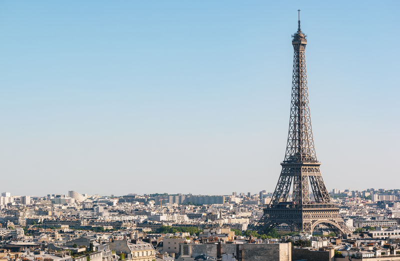 Eiffel Tower Amidst City Against Clear Blue Sky