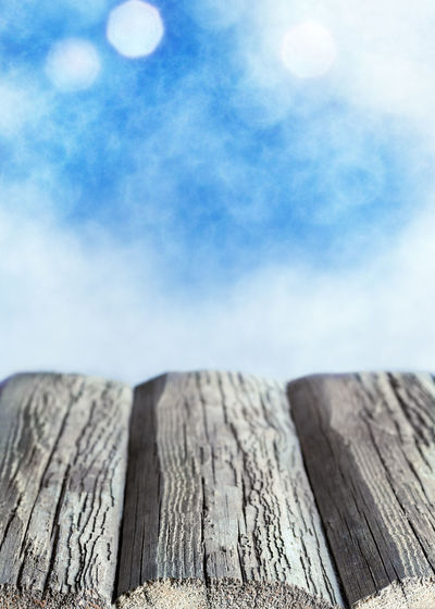 Low angle view of wooden post against sky