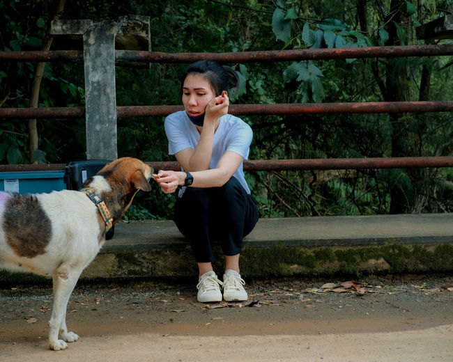Full length of young woman with mask feeding dog outdoors
