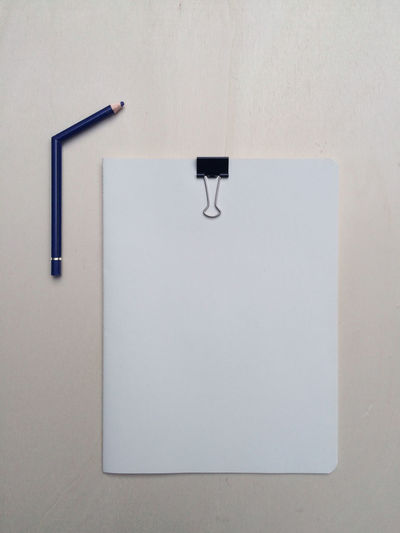 Directly above view of papers with binder clip by broken pencil on table