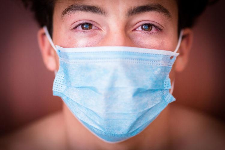 Close-up portrait of teenage boy wearing mask