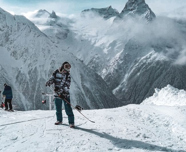 People standing on snowcapped mountain during winter