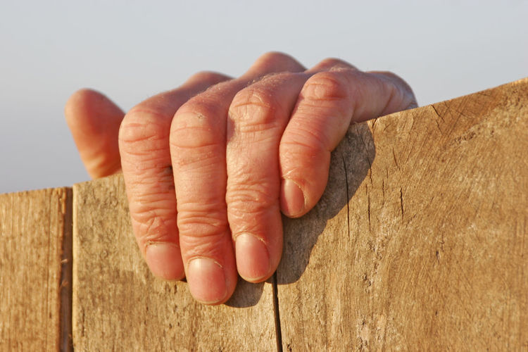 Close-Up Of Human Hand Gripping Onto Wooden Surface