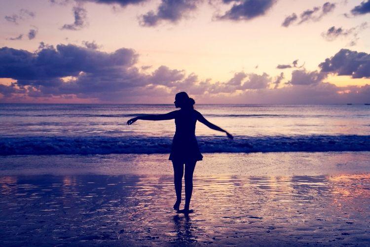Full length of silhouette ballerina dancing at beach against sky during sunset