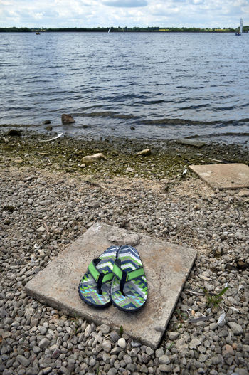 Abandoned Absence Beauty In Nature Boat Day Drab Empty Flipflops Green Color Grubby Idyllic Lakeshore Nature No People Outdoors Plant Rippled Scenics Shoes Thongs Tranquil Scene Tranquility Water
