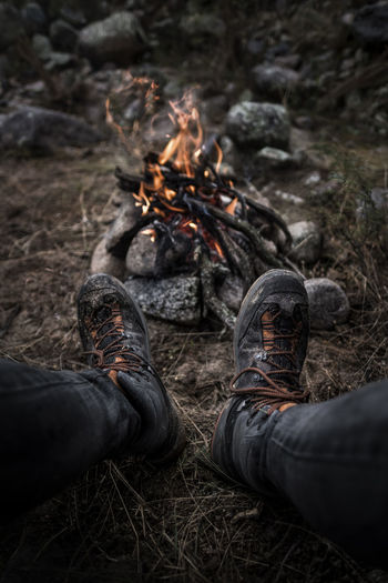 Low Section Of Man Wearing Shoes By Campfire On Field