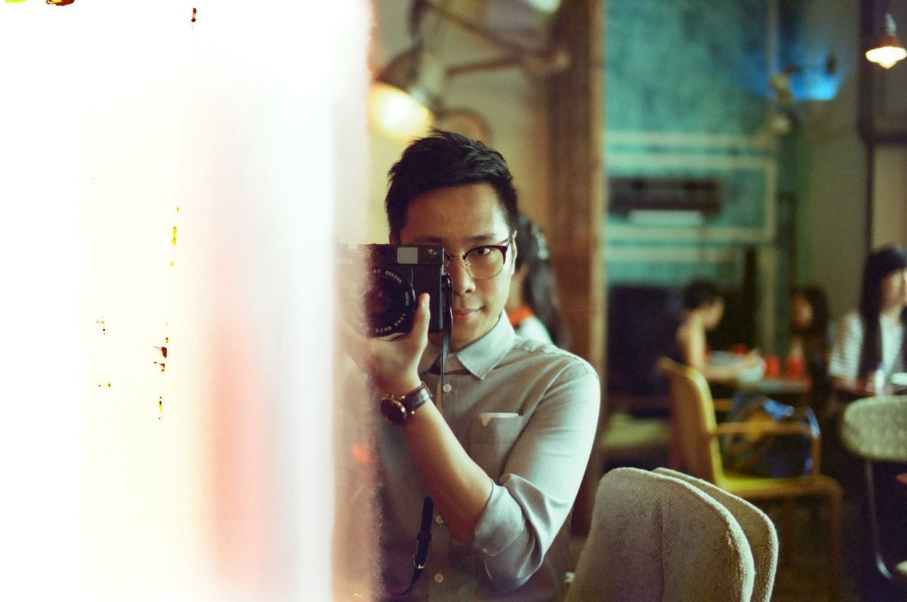 Young man photographing through camera while standing in restaurant