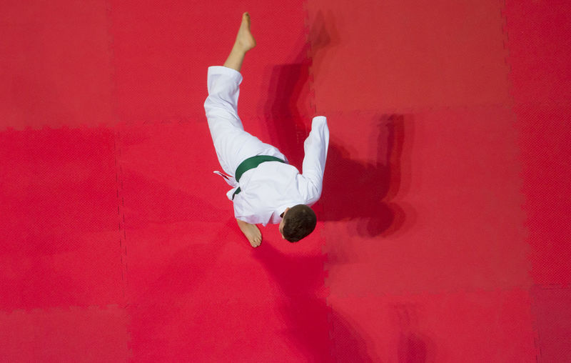karate do boy against red background. Top View. Sport competition. Karate Tatami Kimono Fighter Plane Shape Top Sport Active One Person Full Length Red Men Real People Skill  Indoors  Lifestyles Upside Down Leisure Activity Casual Clothing White Color Wall - Building Feature Vitality Directly Above Copy Space Colored Background Jumping Motion Human Arm Arms Raised Hand Raised